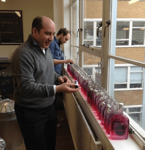 Hugo and Chris stand in front of a row of 30 to 40 bottles of gin on a window sill, adding pink food colouring.