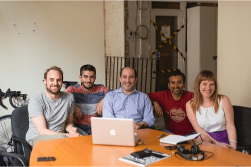 The founders sit at a laptop, with two freelancers beside them, smiling.
