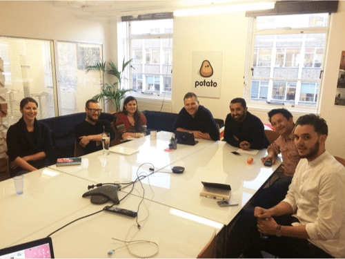 Seven new YunoJuno staff members sit around a conference table, smiling.