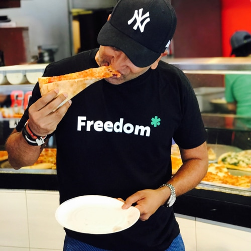 Shib eats a slice of pizza wearing a YunoJuno branded t-shirt and a NY cap, in a New York pizzeria.
