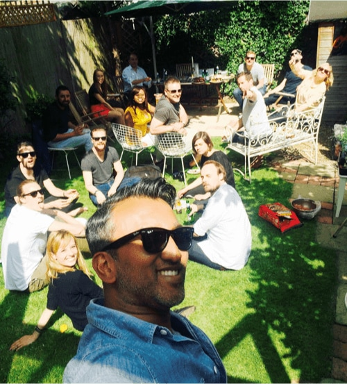Shib takes a selfie with a large group of YunoJuno staff in the background, enjoying themselves in a garden, having a BBQ.