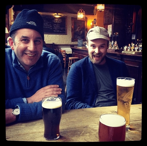 Hugo and Chris sit at a table in a pub, smiling, with several beers on the table.