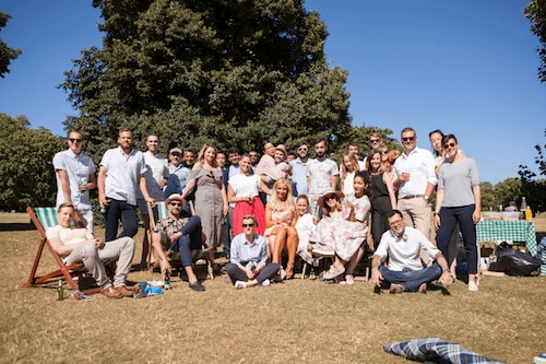 The whole YunoJuno team, around 35 people, pose for the camera in the sun, during the YunoJuno summer party.