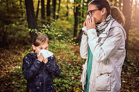 Mother and daughter in forest blowing noses