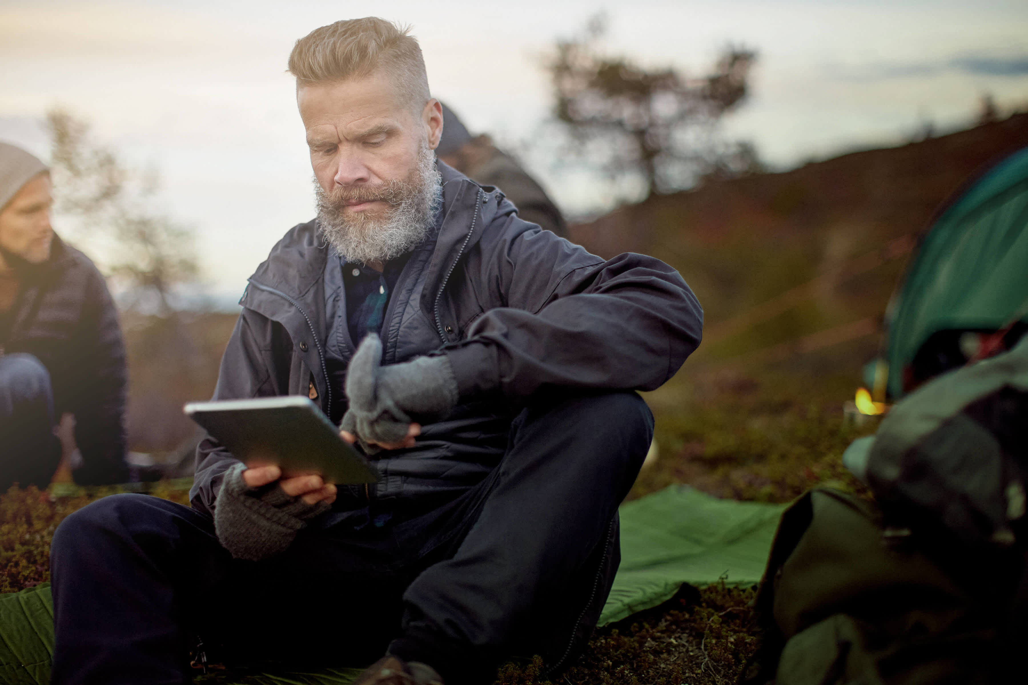 A man is out in the wilderness looking at his tablet.