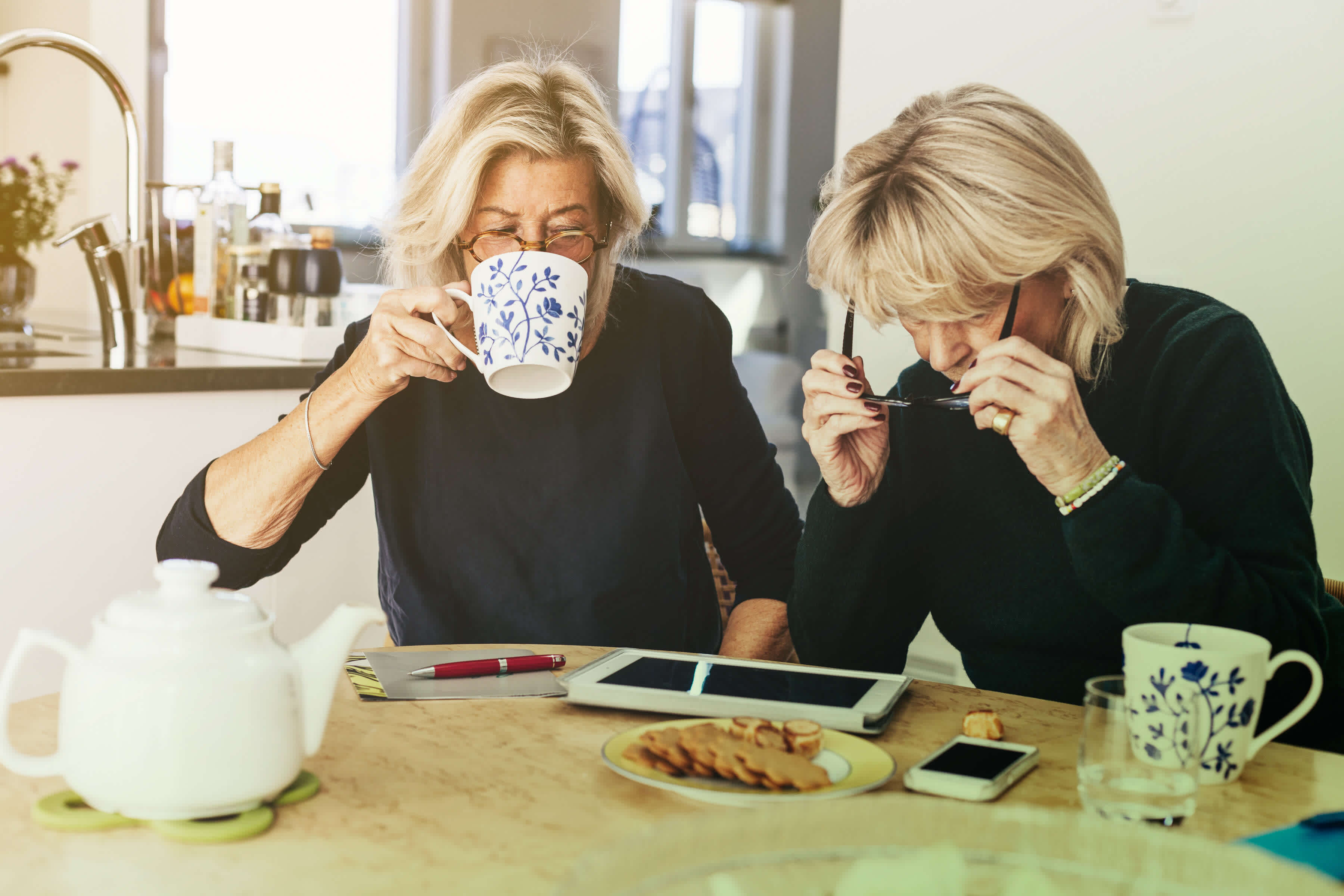 Two women are sitting at a kitchen table having coffee, while working on an iPad.