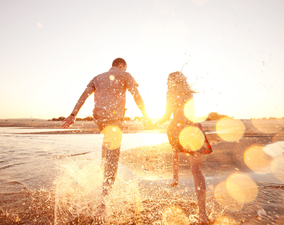 couple-running-through-water-on-sunny-day-i-screen