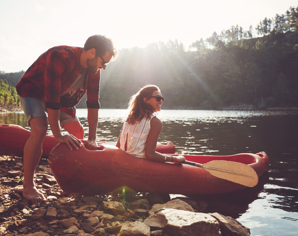 couple-laughing-as-they-prepare-to-canoe-i-screen