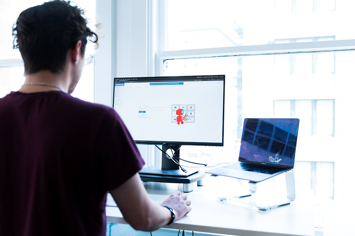 Sauce Labs employee working with two screens