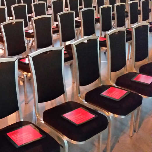 Custom Event App running on iPads neatly placed on chairs in auditorium