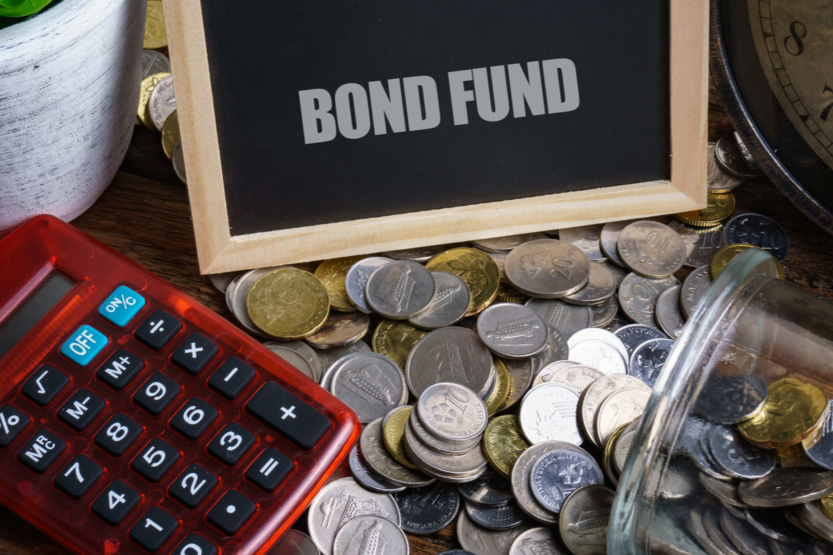 Word BOND FUND on mini chalkboard and coin in the jar