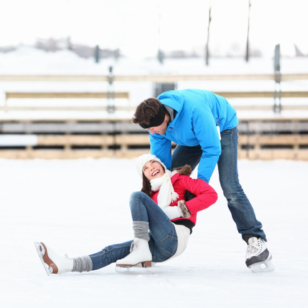 Man helping a female stand up while ice skating