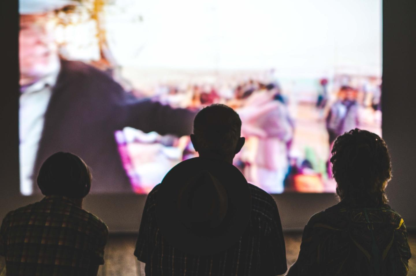 people watch a move in a big screen