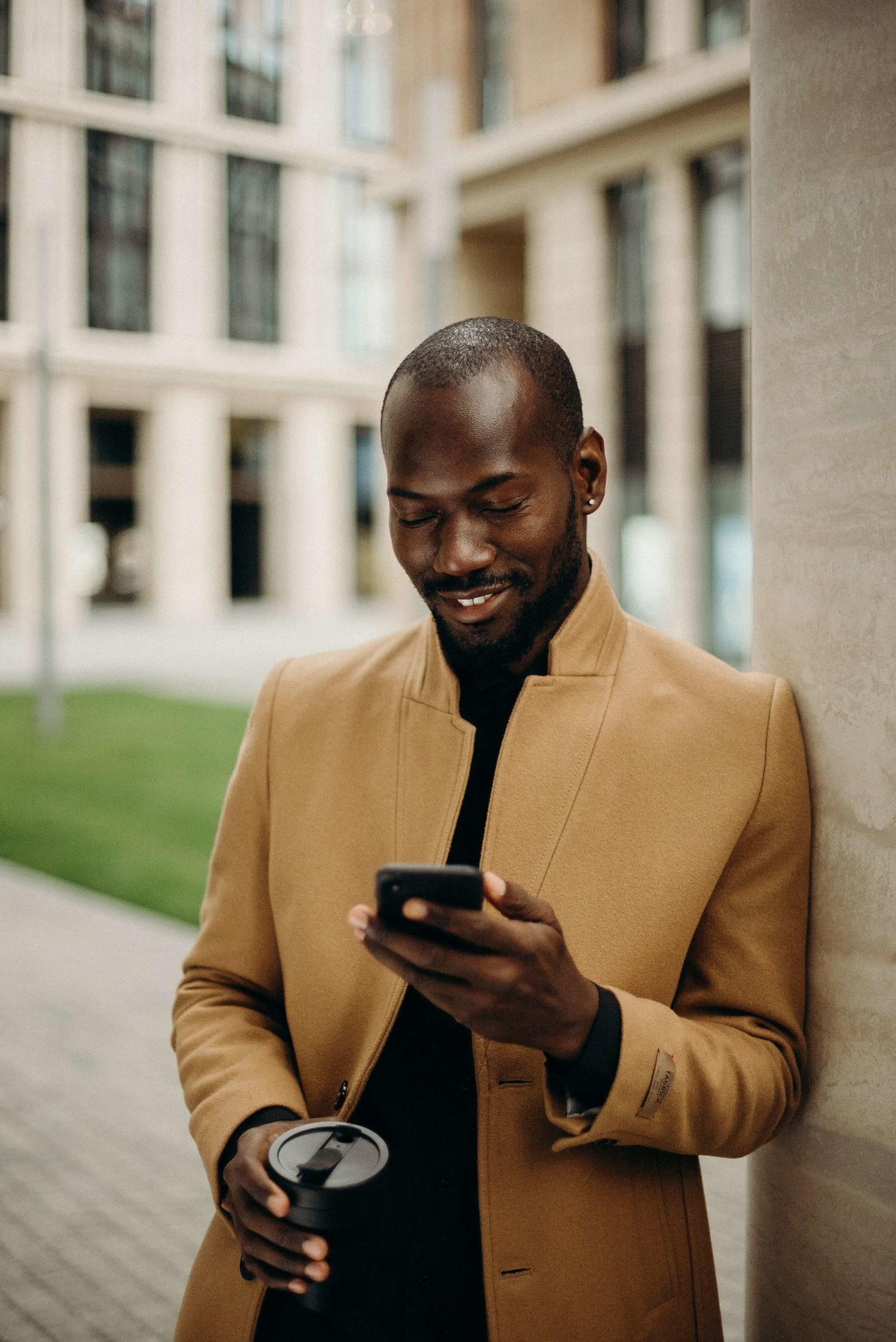 selective focus photo of smiling man looking at his phone
