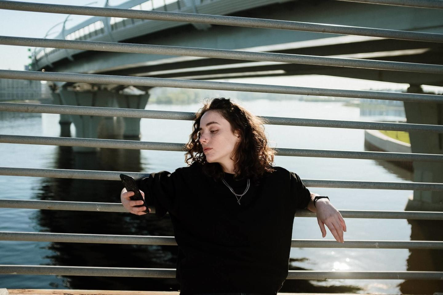 Person looking at phone while leaning on railing