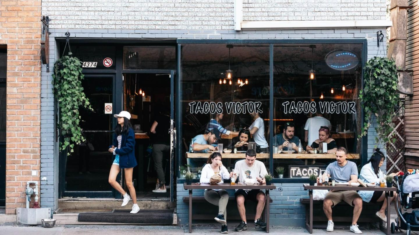 image of a busy taco place with 4 people eating outside, one leaving and many inside.