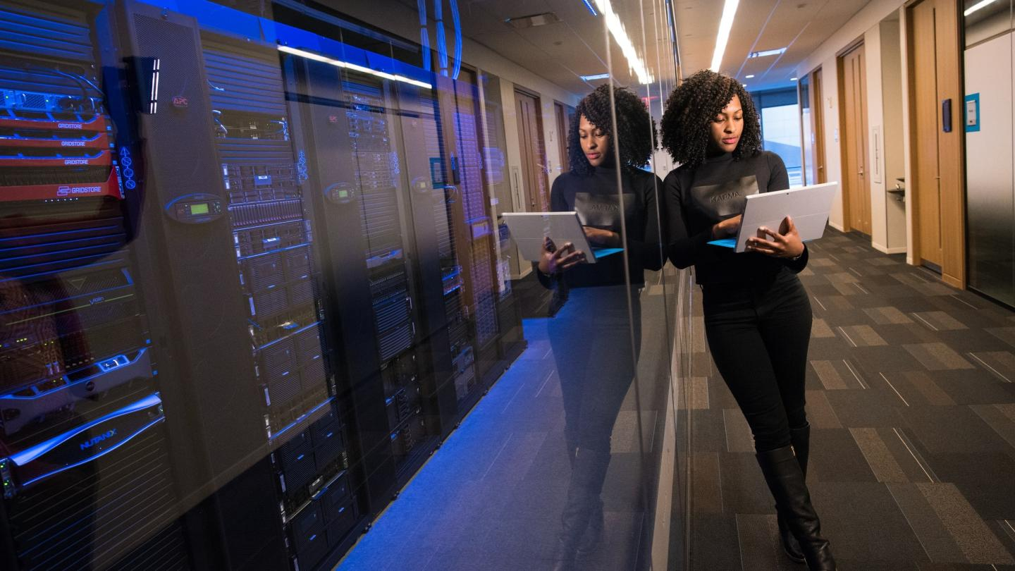 Image of a woman leaning on a glass wall with servers behind it holding a laptop.