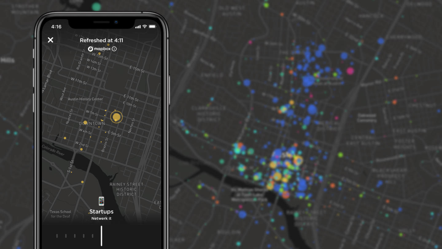 An image of a black map in the background with a phone in front of it with circles on it representing the amount of people at a given place.