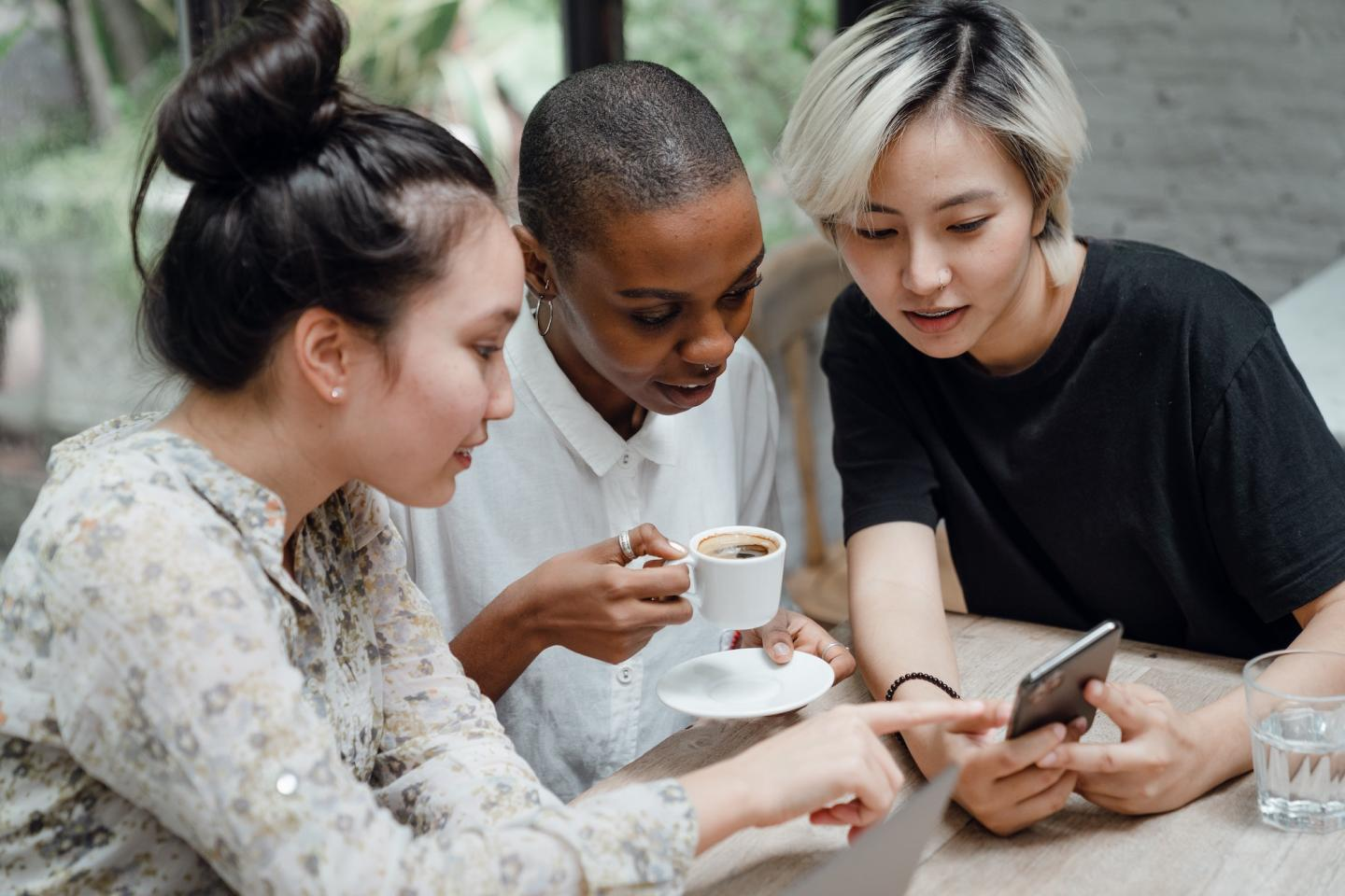 3 women drinking coffee and looking at a phone