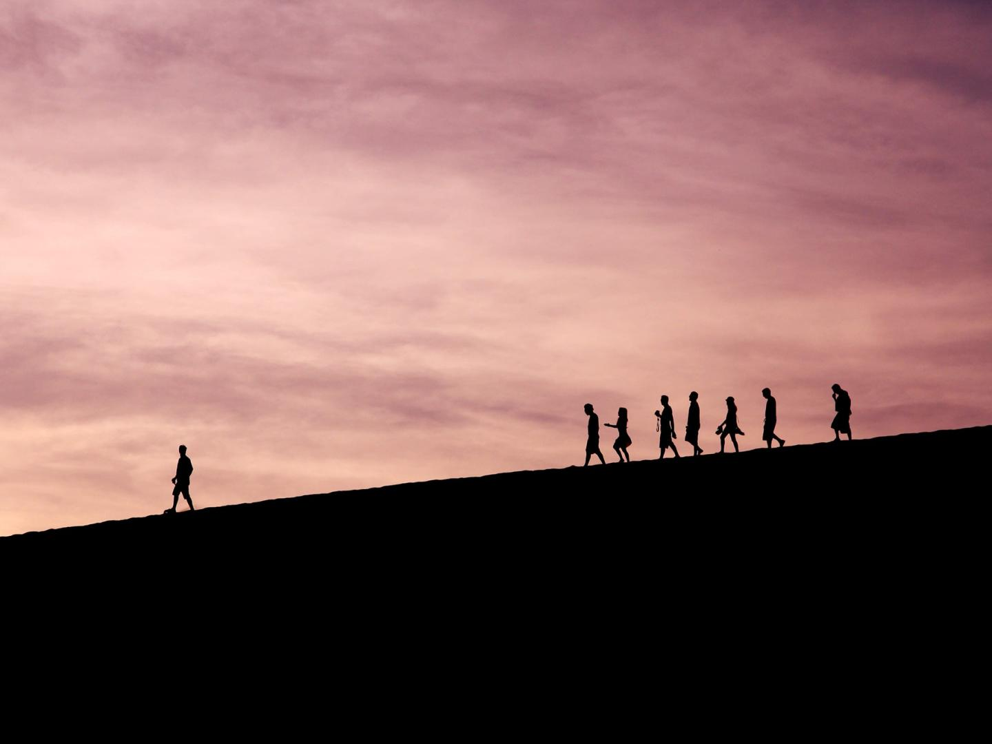 Image of people in distance walking on a hill with one person leading
