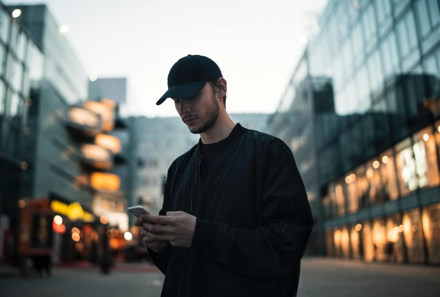A man in a cap looking at his phone with blurred buildings behind him