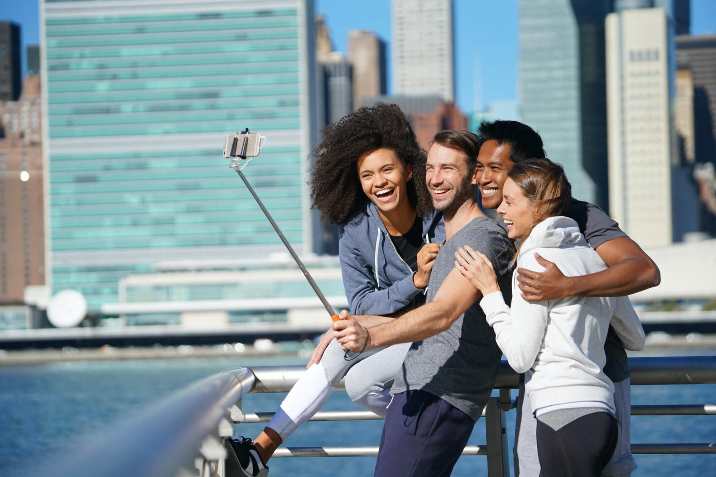 Image of a group of friends taking a picture with a selfie stick with manhattan behind them.