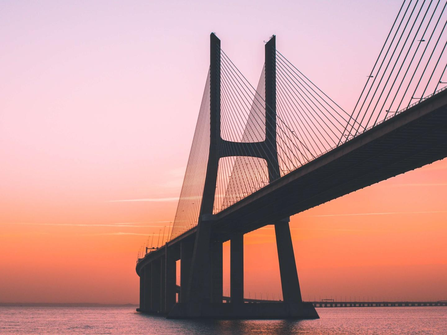 Image of a bridge over water at sunset