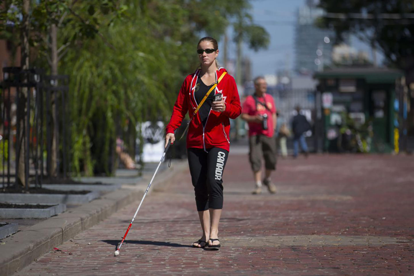 An image of a blind woman walking with a seeing stick holding a phone