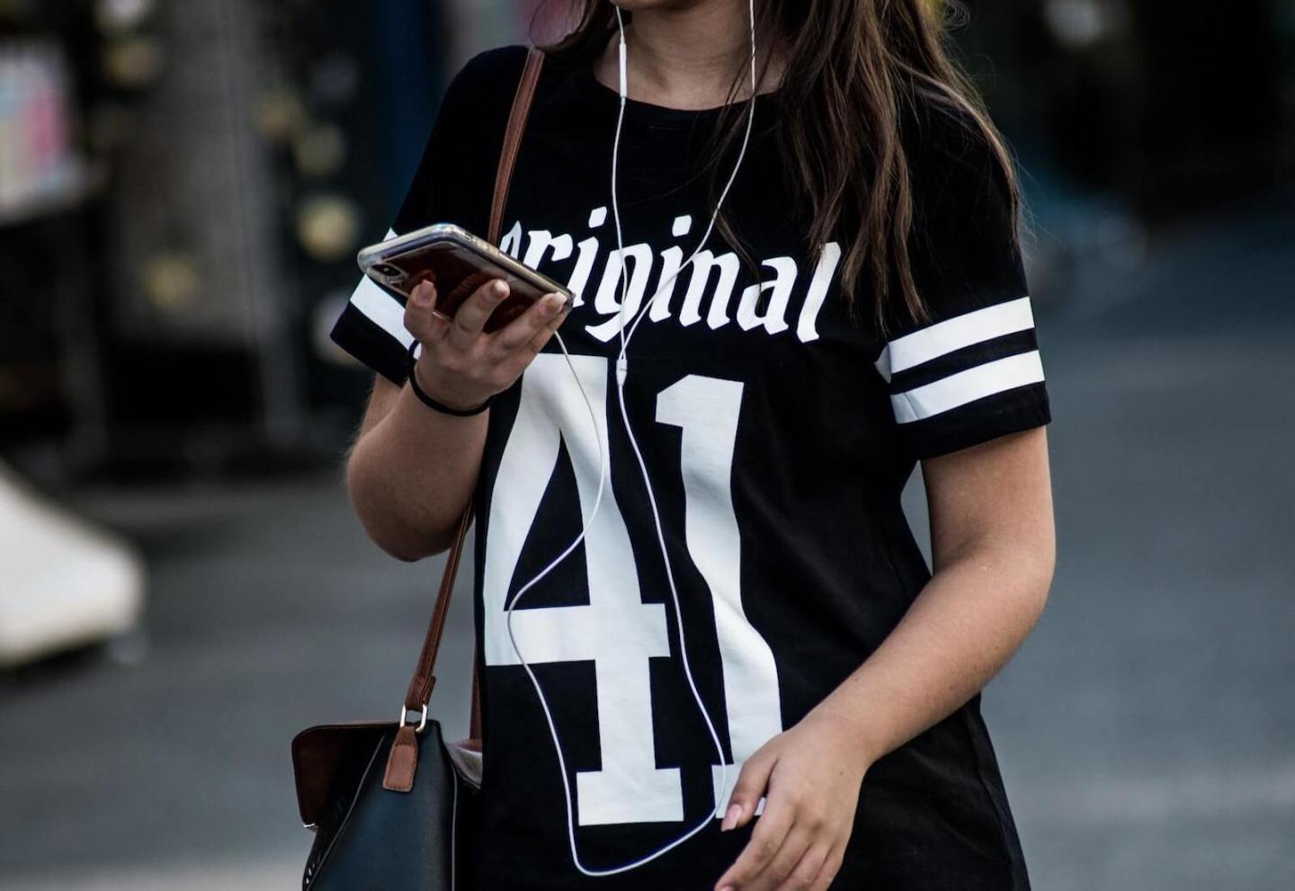 Image of woman walking using a phone with headphones - cropped from neck to waist to focus on the phone