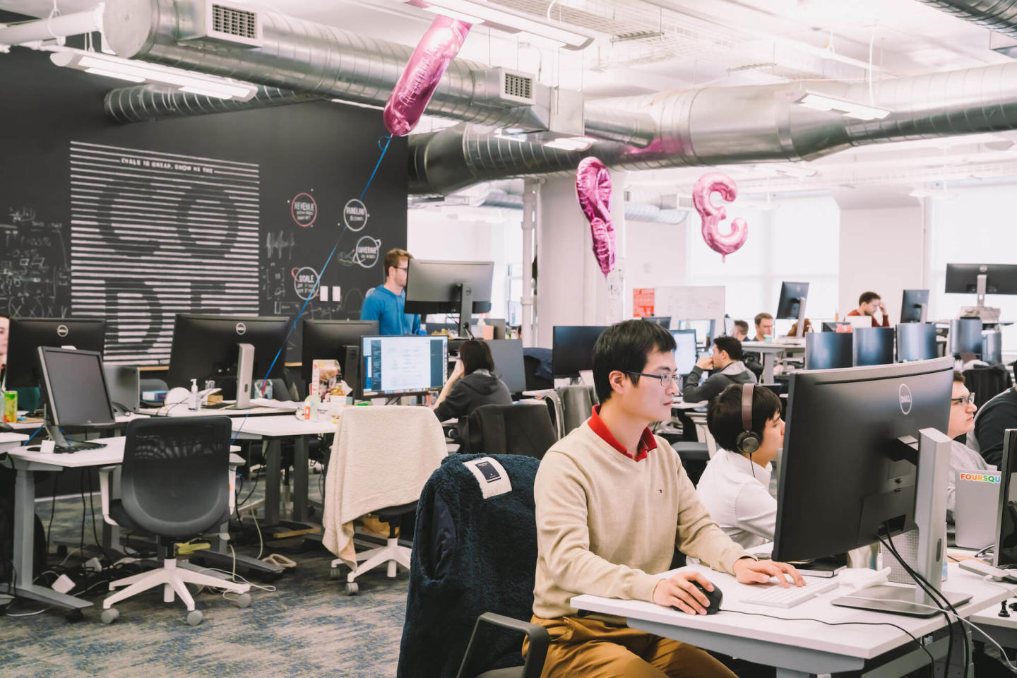 An image of many engineers in an office with pink balloons