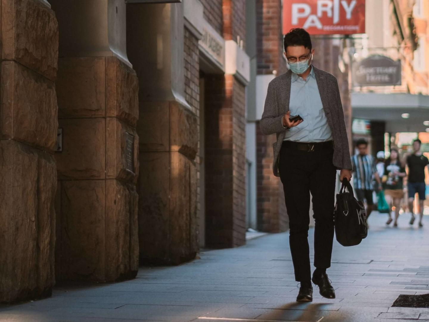 an image of a person wearing a mask walking down a street looking at their phone