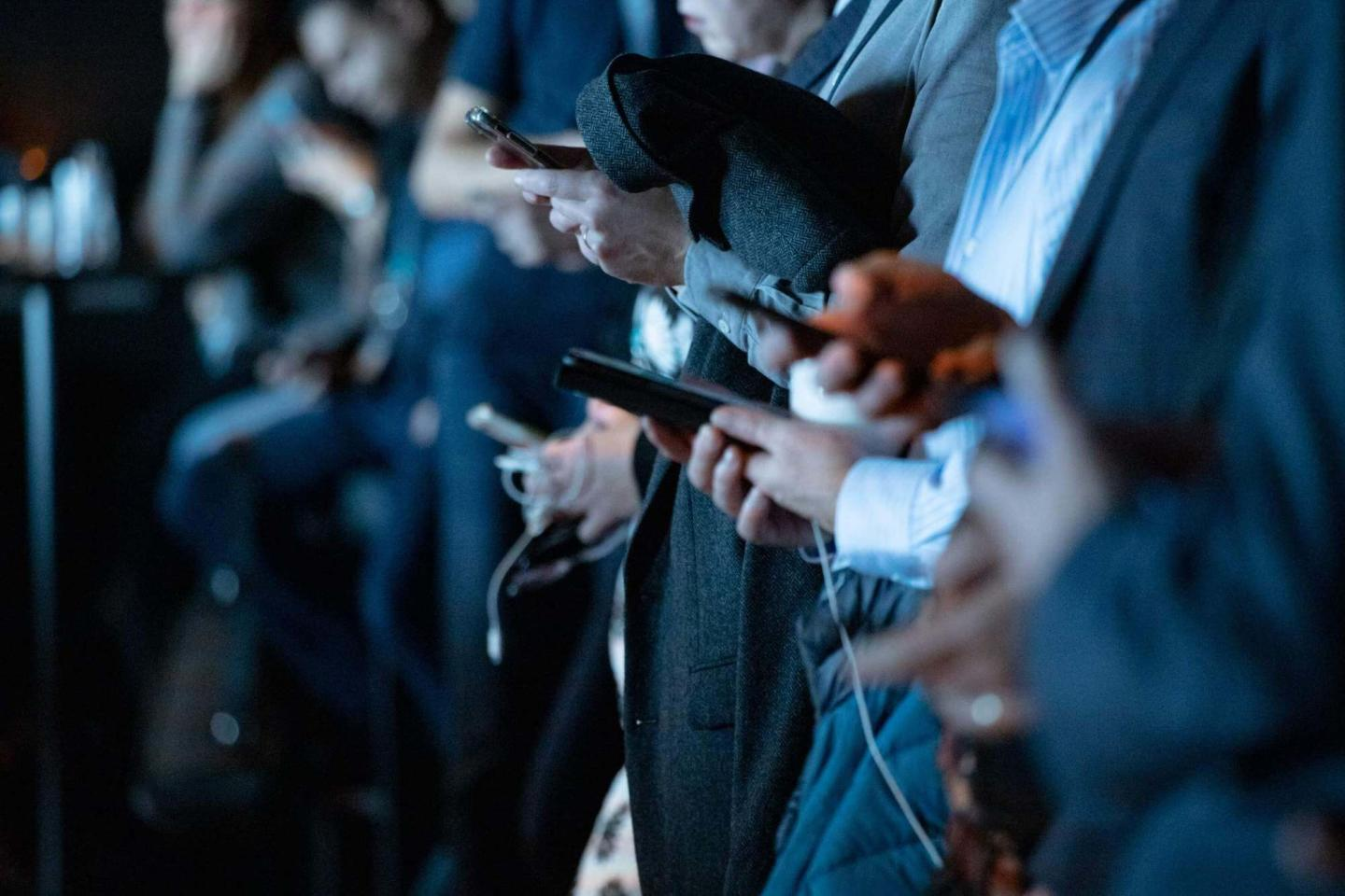 An image of many people on their phones, cropped at the neck and legs.
