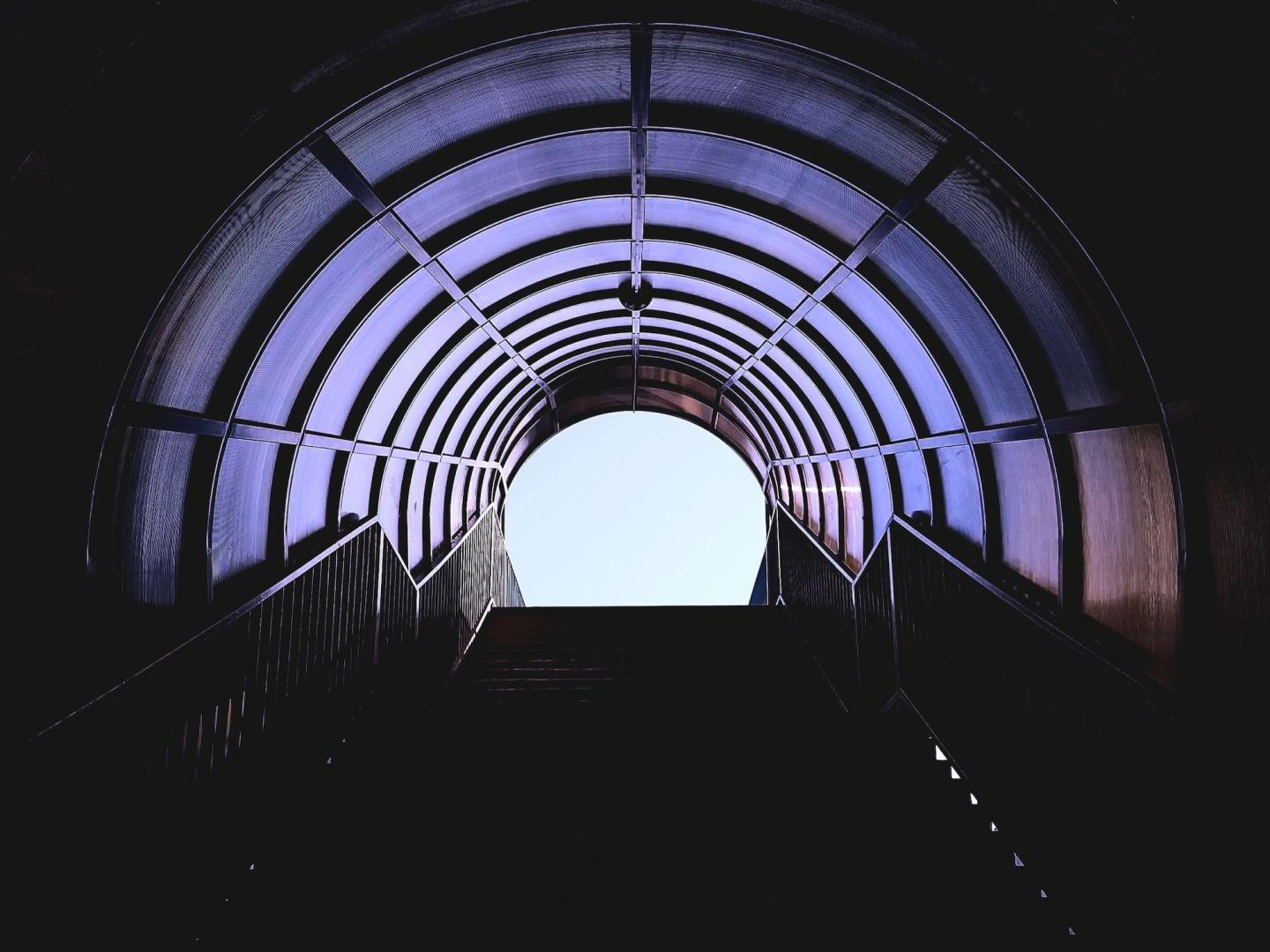 Image of stairs going up in a tunnel with a light ahead