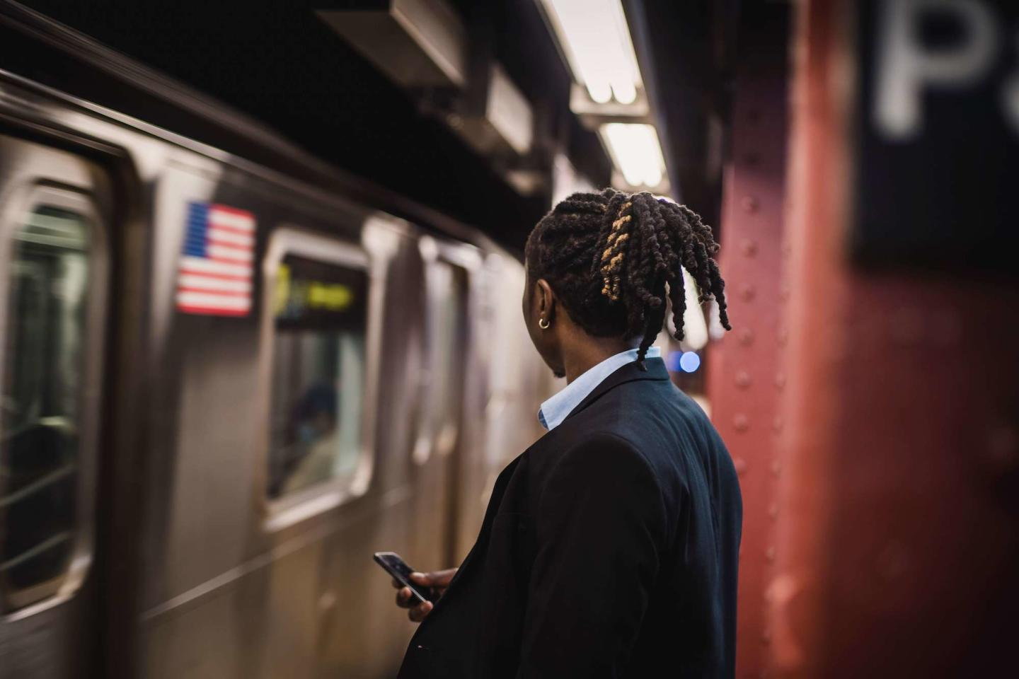 A man waiting for the New York Subway holding his phone