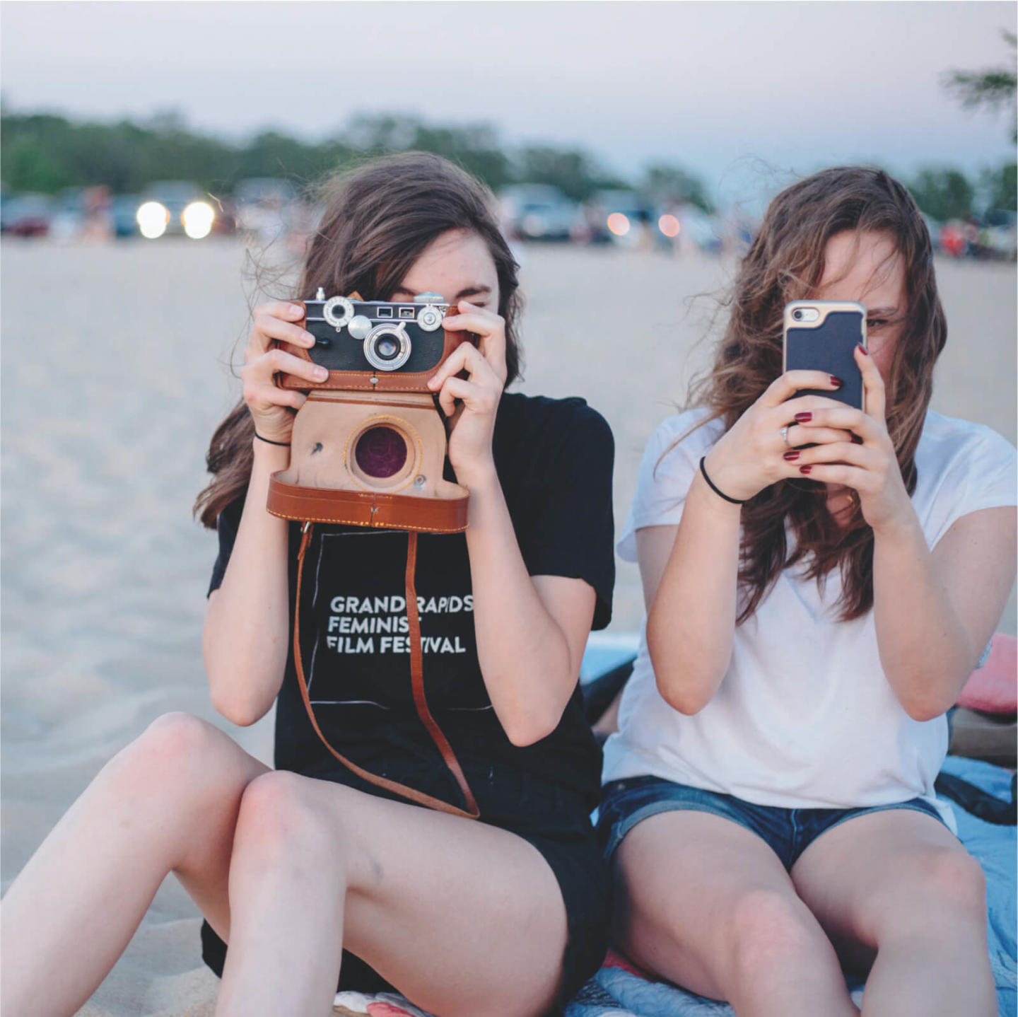 An image of two girls with camera and phone