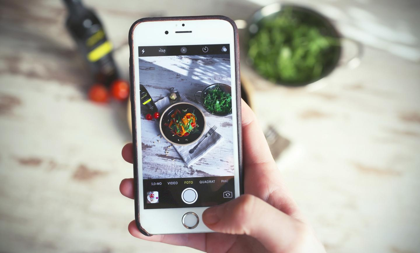Top-down view of a person taking a picture of a salad