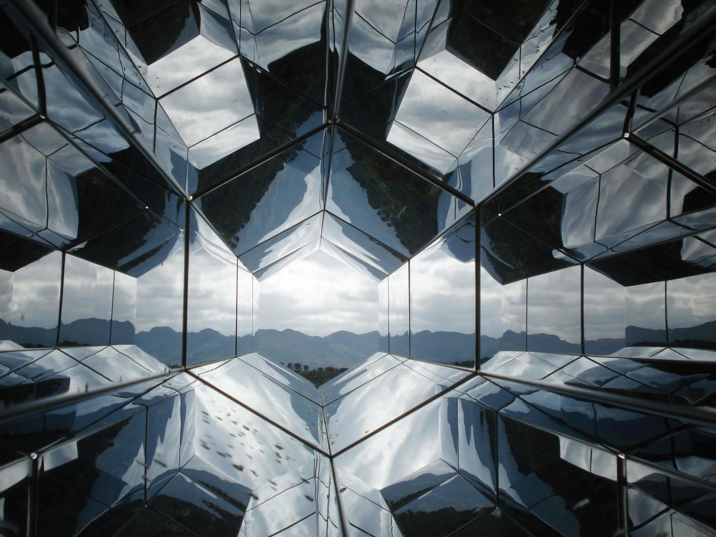 a kaleidoscope-like image looking to mountains through a metal-like structure.