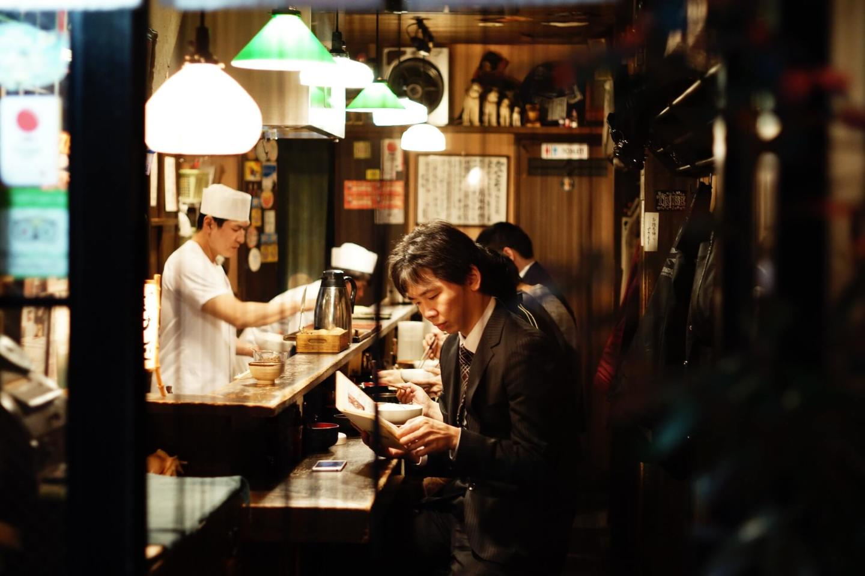An Image of a man reading a menu at a Japanese restaurant