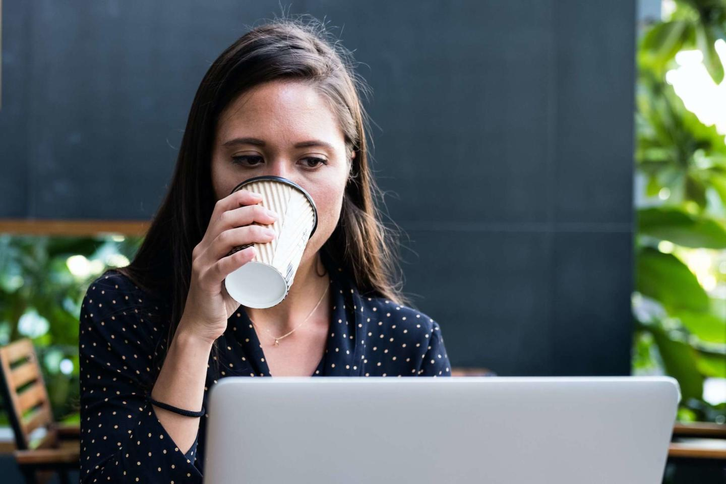 woman drinking coffee while on computer