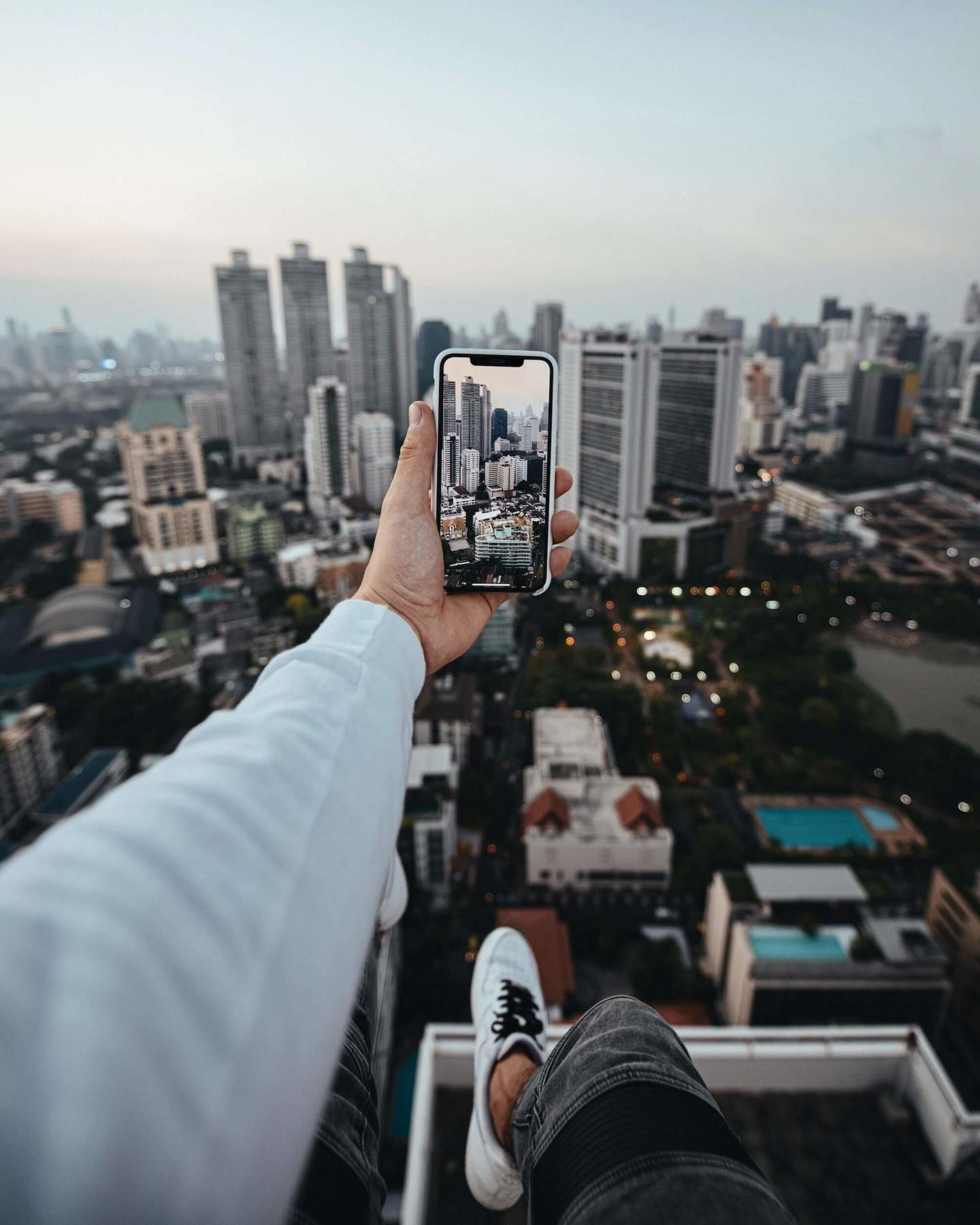 point-of-view image of a person sitting on a tall building taking a photo of other buildings with their phone
