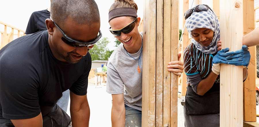 Grupo de pessoas construindo uma casa
