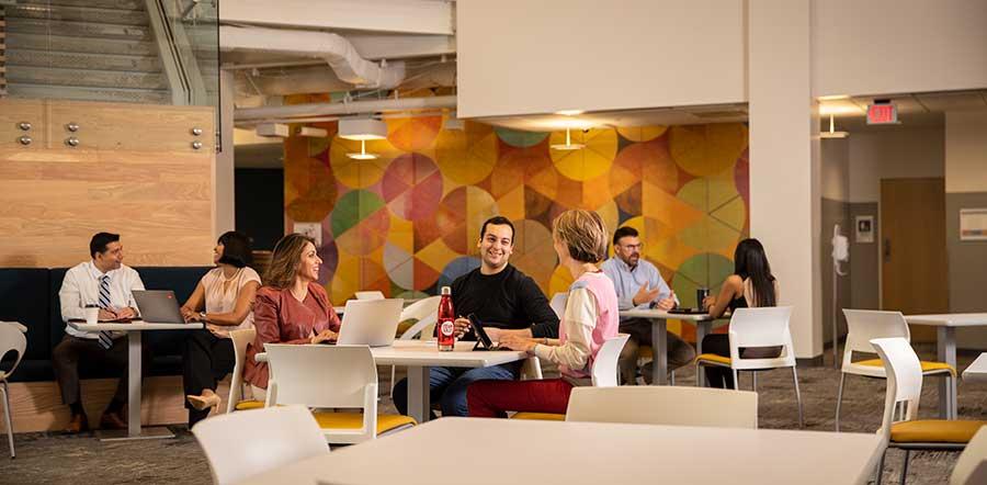 Grupos de pessoas diferentes se encontrando em uma área aberta do escritório