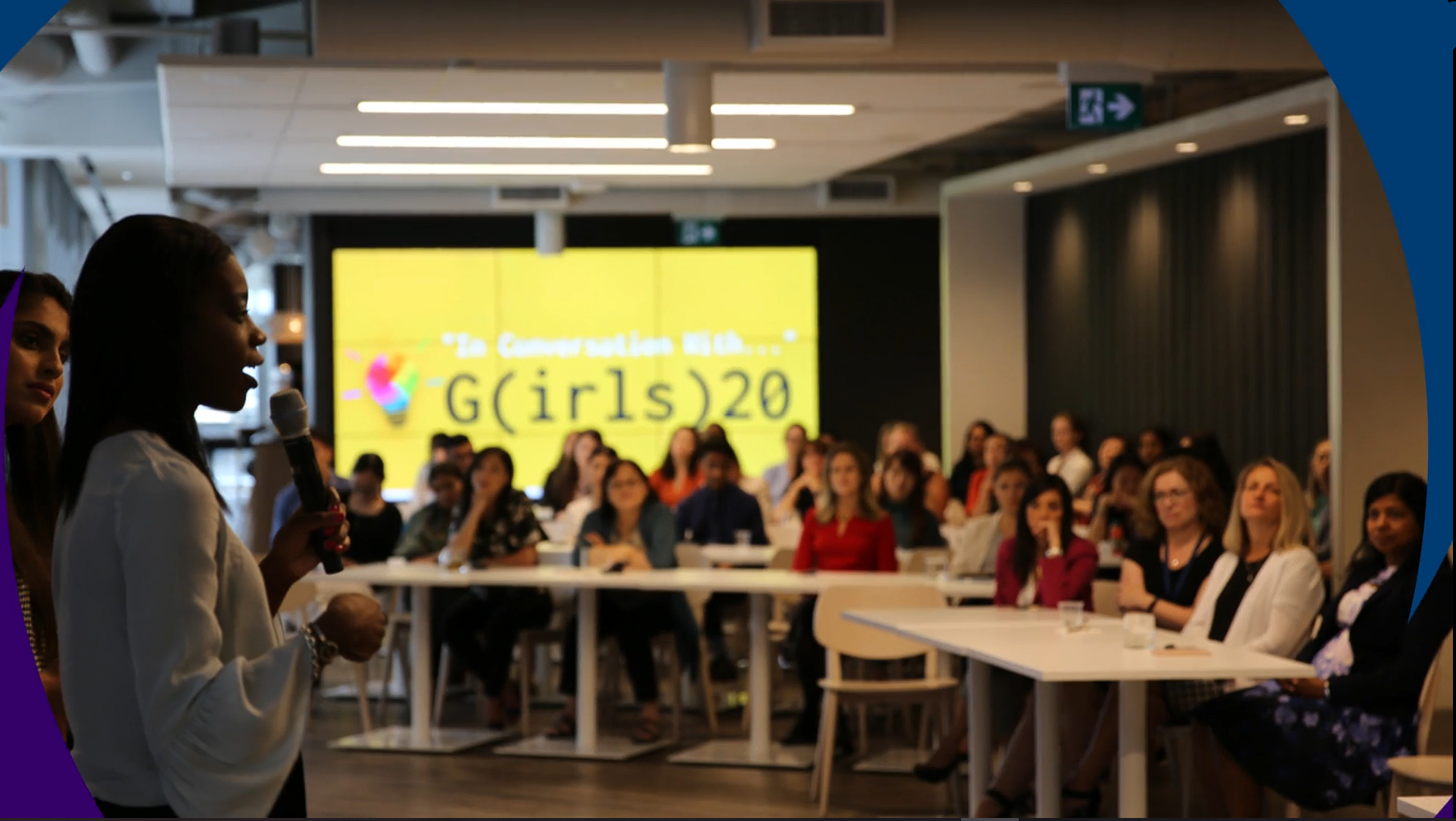 A young woman presenting in front of a group of people in an office for the G(irls)20