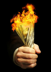 Man holding burning dollars