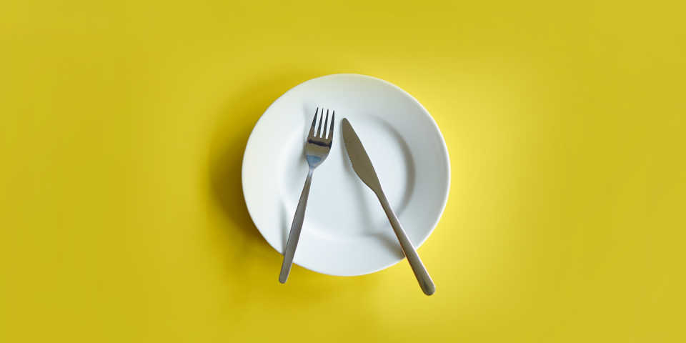 A plate with a knife and fork, but no food.