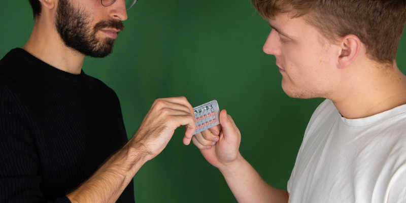 Two men with a pack of birth control pills