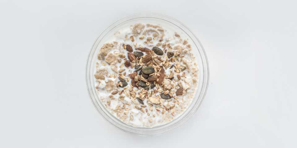 Pumpkin seeds and almonds on top of granola, in a glass of milk.