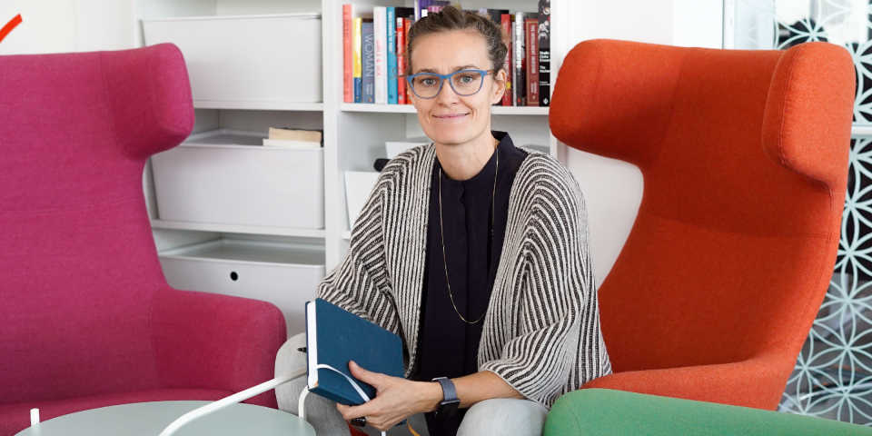 CEO of Clue Ida Tin sitting in her office holding a notebook.