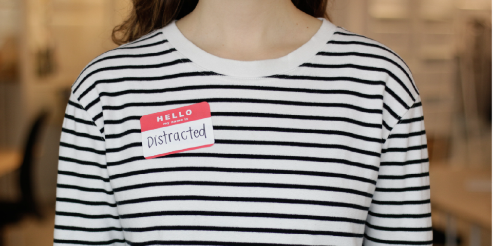 close up photograph of a woman wearing a striped shirt and a stickers saying hello my name is distracted in front of a blurry background