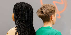 Photo of two people standing back-to-back with their hair